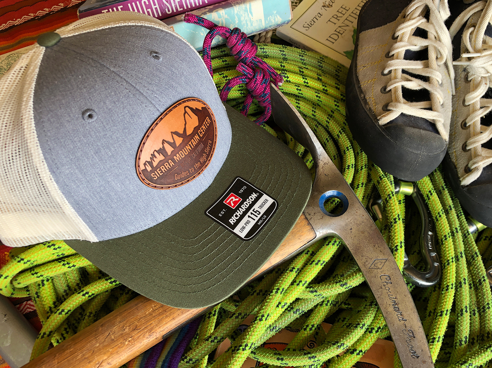 Pile of new and vintage climbing gear and Sierra Nevada books, trucker hat on top